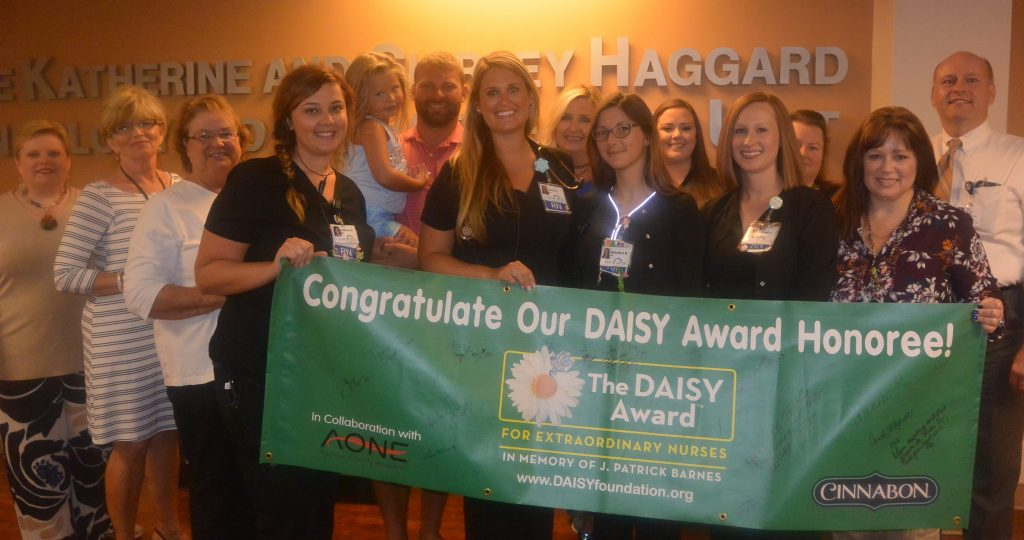 Co-workers and family of Catie Shaw congratulating her on being the June 2019 DAISY award recipient.